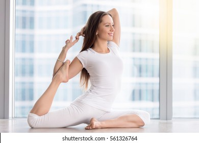 Young smiling woman practicing yoga, sitting in One Legged King Pigeon exercise, Eka Pada Rajakapotasana pose, working out, wearing sportswear, white t-shirt, pants, indoor full length