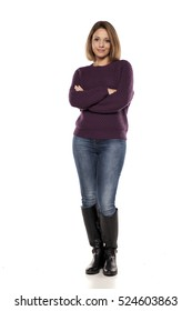 young smiling woman in a purple sweater and jeans with crossed arms