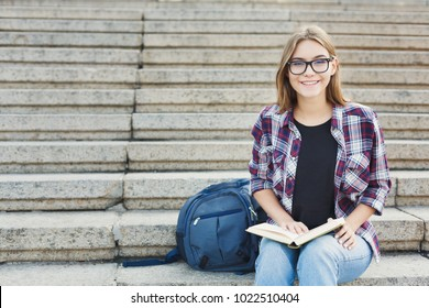 Young smiling woman reading book on university stairs, preparing for exams at college. Education concept, copy space