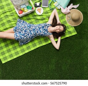 Young smiling woman relaxing outdoors and having a picnic, she is lying down on a blanket on the grass