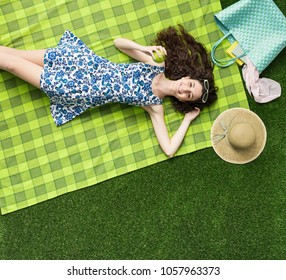 Young smiling woman relaxing at the park, she is eating an apple and lying on the grass