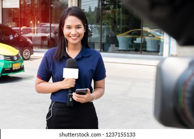 Young smiling woman reports standing with microphone on urban background