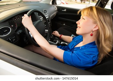 Young smiling woman sitting in car and driving
