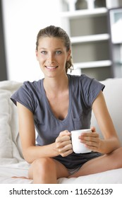 Young smiling woman sitting with a cup of coffee