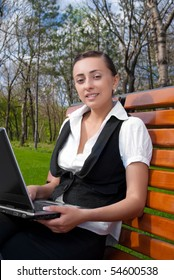 Young smiling woman sitting on bench with laptop