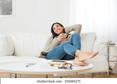 Young smiling woman sitting on sofa and looking up while drinking hot tea. Young brunette woman thinking at home in a leisure time. Happy girl relaxing at home on a bright winter morning. - Shutterstock ID 555045271