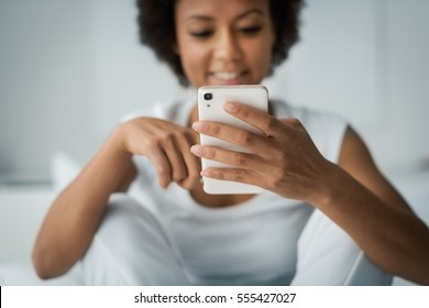 Young smiling woman sitting on the bed at home and texting with her smartphone, she is social networking and chatting