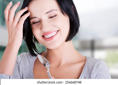 Young smiling woman with spoon.
