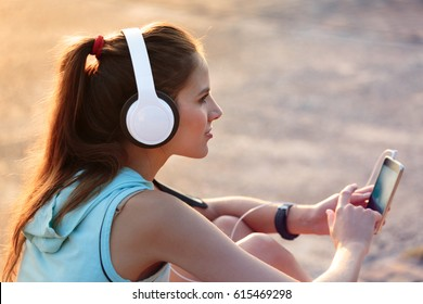 Young smiling woman with sporty clothes listening to music with headphones from her smart phone at the park during at sunset
