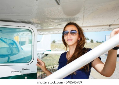 Young smiling woman standing near private plane ready for flight