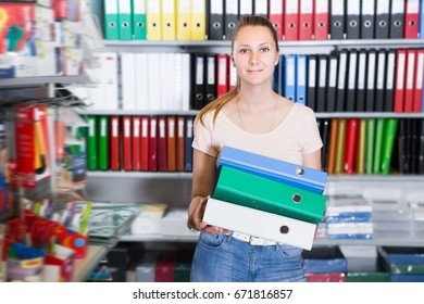 Young smiling woman standing in stationery store with folders