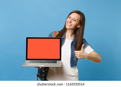 Young smiling woman student with backpack showing thumb up holding laptop pc computer with blank black empty screen isolated on blue background. Education in university. Copy space for advertisement