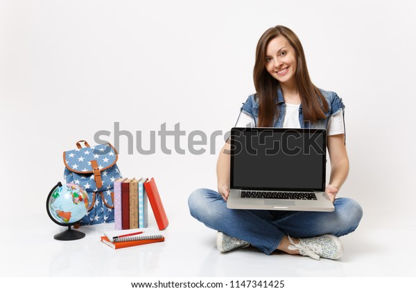Young smiling woman student holding laptop pc computer with blank black empty screen sitting near globe backpack school books isolated on white background. Education in high school university college