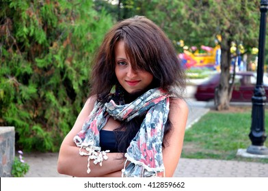 7ae253660b Young smiling woman in summer shawl with floral pattern and brunette hair standing  outdoor in park