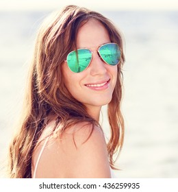 Young smiling woman in sunglasses standing near the sea