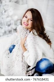 Young smiling woman in sweater, winter holidays in decorated home interior with Christmas tree.