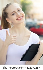 Young smiling woman with tablet shows thumb up