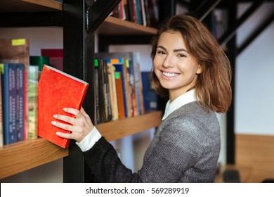 Young smiling woman taking book from library shelf and looking at camera