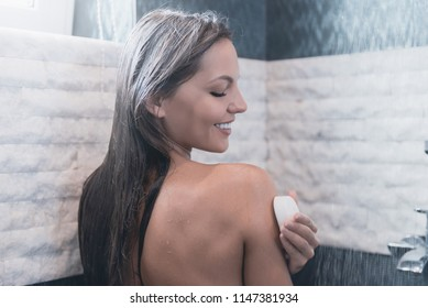 Young Smiling Woman Taking Shower her Eyes Closed with Pleasure. Pleasant Water Running. Beauty Concept Photo. Cute Brunette Washes with Soap in Bathroom. Personal Hygiene at Morning.