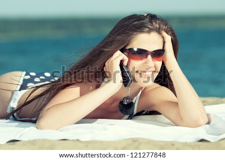 Young smiling woman talking by phone on a beach