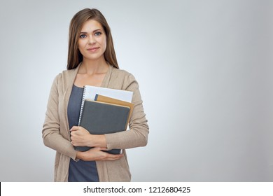 Young smiling woman teacher holding work books. Isolated studio portrait.