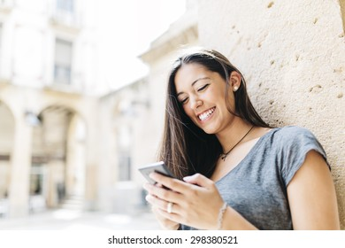Young smiling woman text messaging on mobile phone