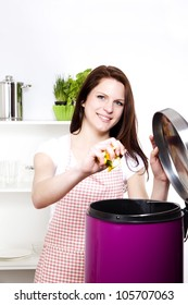 young smiling woman throwing away some organic waste