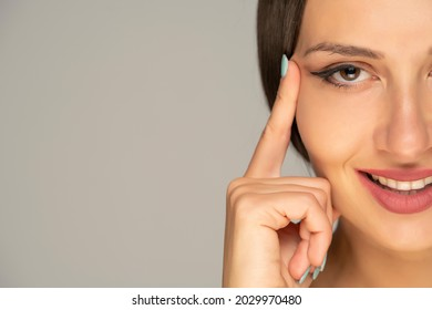 Young smiling woman tightening her face skin with her fingers on a gray background