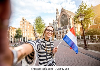 Young smiling woman tourist making selfie photo standing with dutch flag on the bridge near the Old church in Amsterdam city