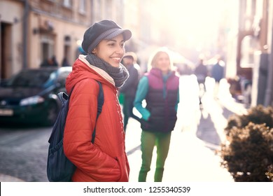 young smiling woman tourist in red jacket, gray scarf and cap walking outdoors with friends on the street of old Lviv at sunny autumn or spring day