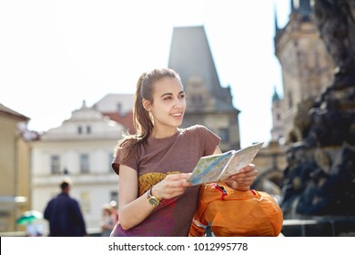 a young smiling woman tourist in sportswear and small orange backpack in the center of Prague with a map in the hands of. travel guide, tourism in Europe, woman tourist with map on the street