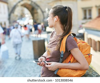 a young smiling woman tourist in sportswear walking in the center of Prague with a phone in the hands of. travel guide, tourism in Europe, woman tourist with smartphone on the street