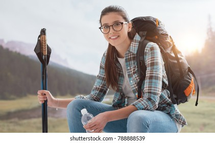 Young smiling woman trekking on the mountains and having a relaxing break, she is sitting and holding hiking poles