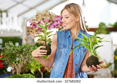Young smiling woman with two kokedama in her hands in a garden center
