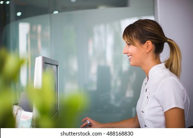 Young smiling woman  using computer at reception of dental clinic.