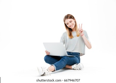 Young smiling woman using laptop computer and shoing peace gesture isolated over white
