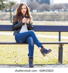 Young smiling woman using smartphone sitting on bench in park. Beautiful european girl texting on phone