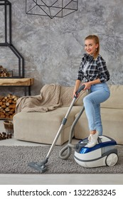 Young smiling woman vacuum cleaning the carpet in the living room, modern scandinavian interior. Home, housekeeping concept