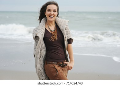 Young smiling woman walking by a sea beach, autumn fashion, healthy lifestyle concept, total happiness