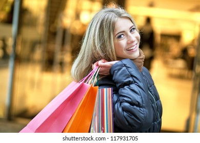 Young smiling woman walking on the street and enjoying shopping