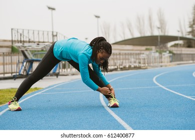 Young smiling woman warming up in the stadium. Horizontal outdoors shot.