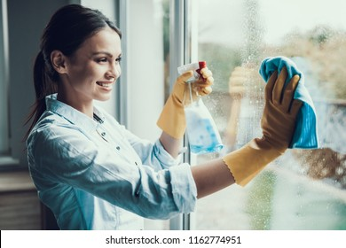 Junge Lächelnde weibliche Waschfenster mit Schwamm. Happy Schönes Mädchen mit Schutzhandschuhen Reinigungsfenster durch Spritzen von Reinigungsprodukten und Abwischen mit Schwamm. Reinigungshaus für Frauen