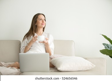 Young smiling woman wearing a dressing gown thinking about a future travel, listening to a favorite musical track via laptop, resting in a hotel room alone, enjoying, planning future