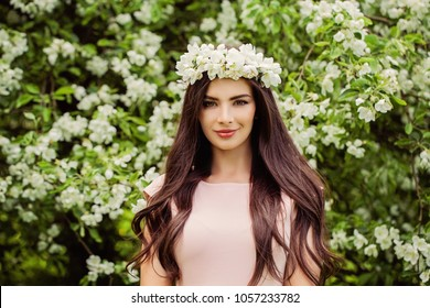 Young smiling woman wearing flowers wreath. Cute girl with makeup, flowers and long smooth hair on floral background outdoors