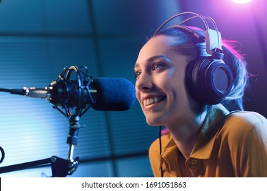 Young smiling woman wearing headphones and talking into a microphone at the radio station, entertainment and communication concept