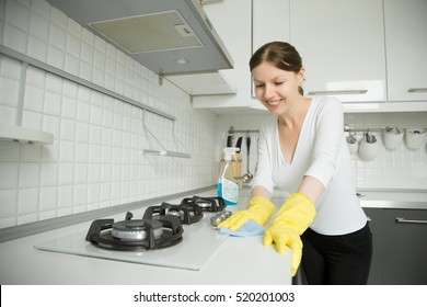 Young smiling woman wearing rubber protective yellow gloves cleaning the stove with a rag and spray bottle detergent. Home, housekeeping concept. Looking at the camera