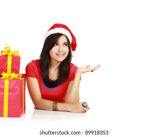 Young smiling woman  wearing Santa Claus hat presenting something in isolated white background