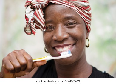 young smiling woman wearing a scarf on the head brushes the tooth