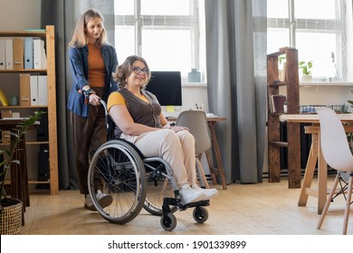 Young smiling woman in wheelchair looking forwards while her sister or friend standing behind and helping her with moving around