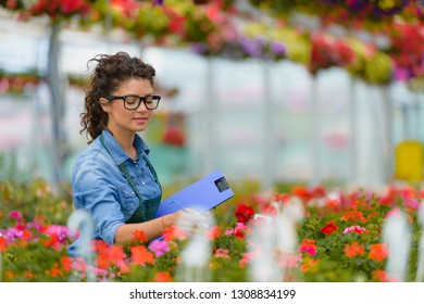 Young smiling woman working in flower garden. Woman Entrepreneur.